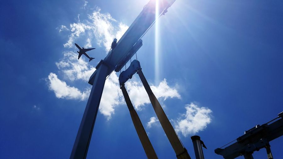 A plane flying over a Crane My Best Photo Aeroplane Transportation Crane Belts Sky Clouds Mode Of Transport Military Airplane