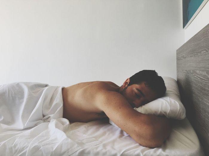Shirtless man lying on bed