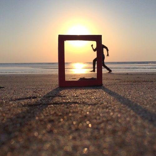 Man running on beach against sky during sunset