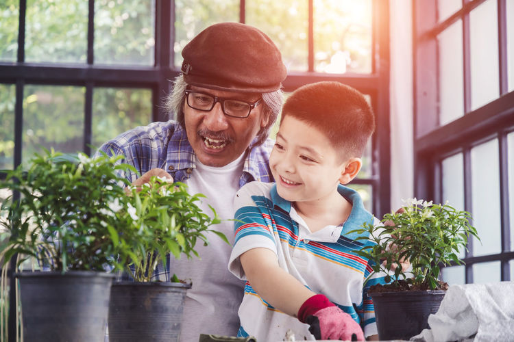 Father and son on potted plant at home