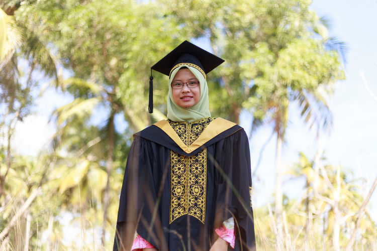 Portrait of young woman wearing hijab and graduation gown standing at park