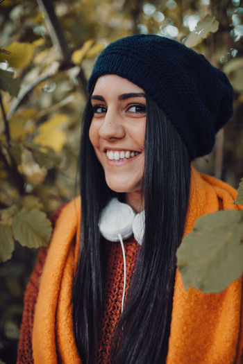 Portrait of smiling young woman standing in forest during winter