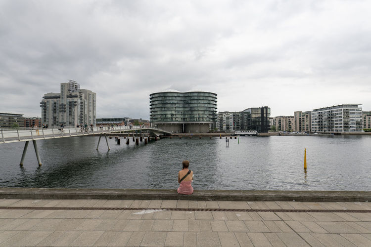Rear view of woman on river by cityscape against sky