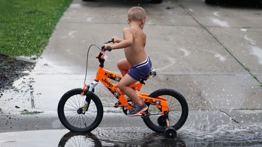 Boy with bicycle on road