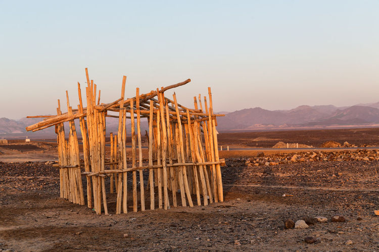 Wooden structure on field against clear sky