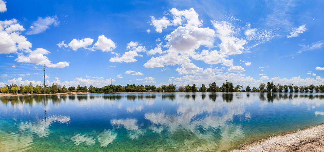 A quiet lake on a summer day Sky Nature Day No People Outdoors Water Reflection Cloud - Sky Lake Tranquil Scene Tranquility Scenics - Nature Beauty In Nature Blue Tree Plant Non-urban Scene Idyllic Waterfront Clean Clouds