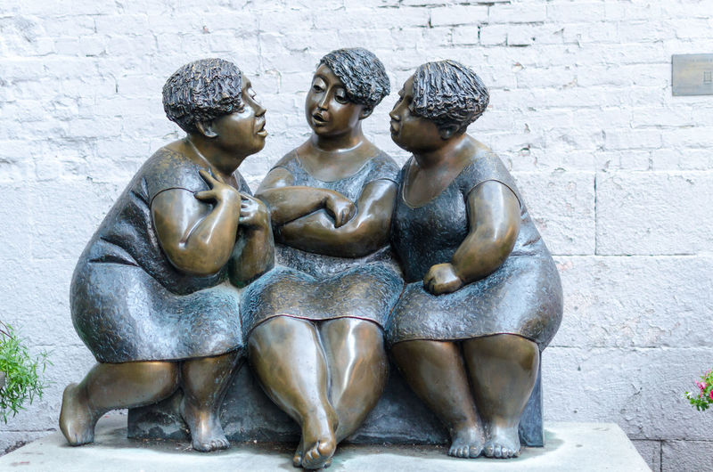 Close-up of les chuchoteuses sculpture against wall