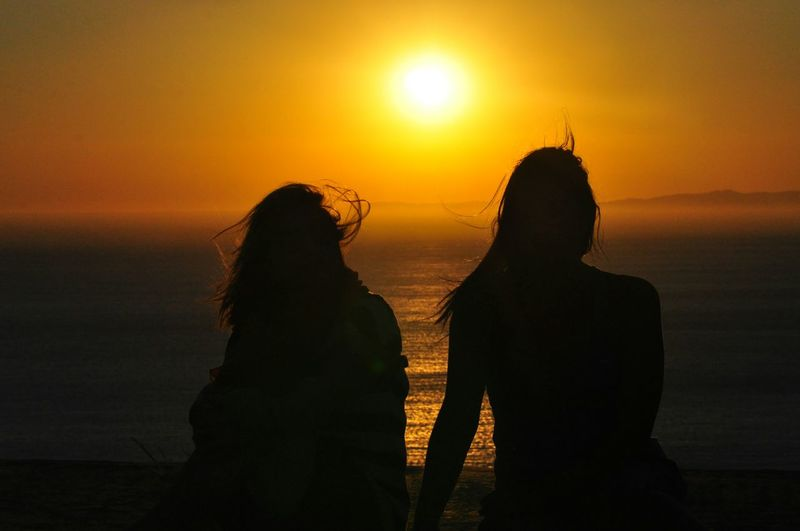 Rear View Of Silhouette Women Against Sky At Beach During Sunset