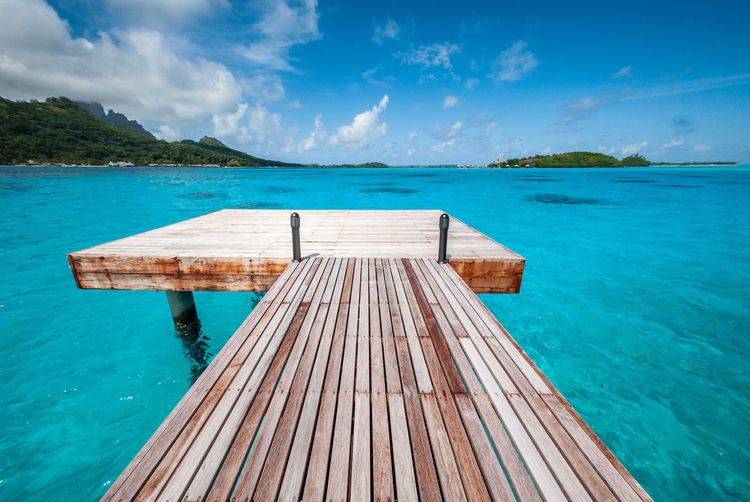 Bora Bora  Beauty In Nature Blue Cloud - Sky Day Empty Idyllic Jetty Nature No People Non-urban Scene Outdoors Pier Scenics - Nature Sea Sky Tahiti The Way Forward Tranquil Scene Tranquility Turquoise Colored Water Wood Wood - Material Wood Paneling