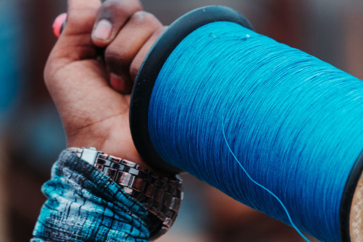 Close-up of hand holding kite spool