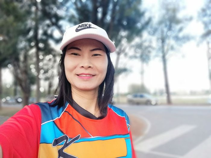 Portrait of smiling woman standing on road