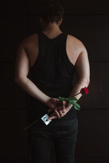 Rear view of man holding rose while standing against wall