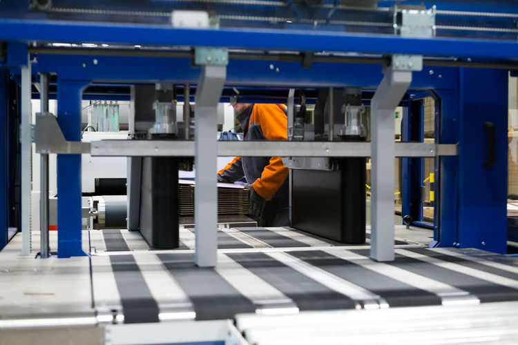 Printing and cutting packaging industry machine Technology Indoors  One Person Real People Occupation Working Architecture Security Standing Adult Business Clothing Orange Color Built Structure Safety Protection Connection Men Rear View Printing Cutting Board Industry Measuring Measurement Factory Horizontal Packaging Industry Cardboard Warehouse Working