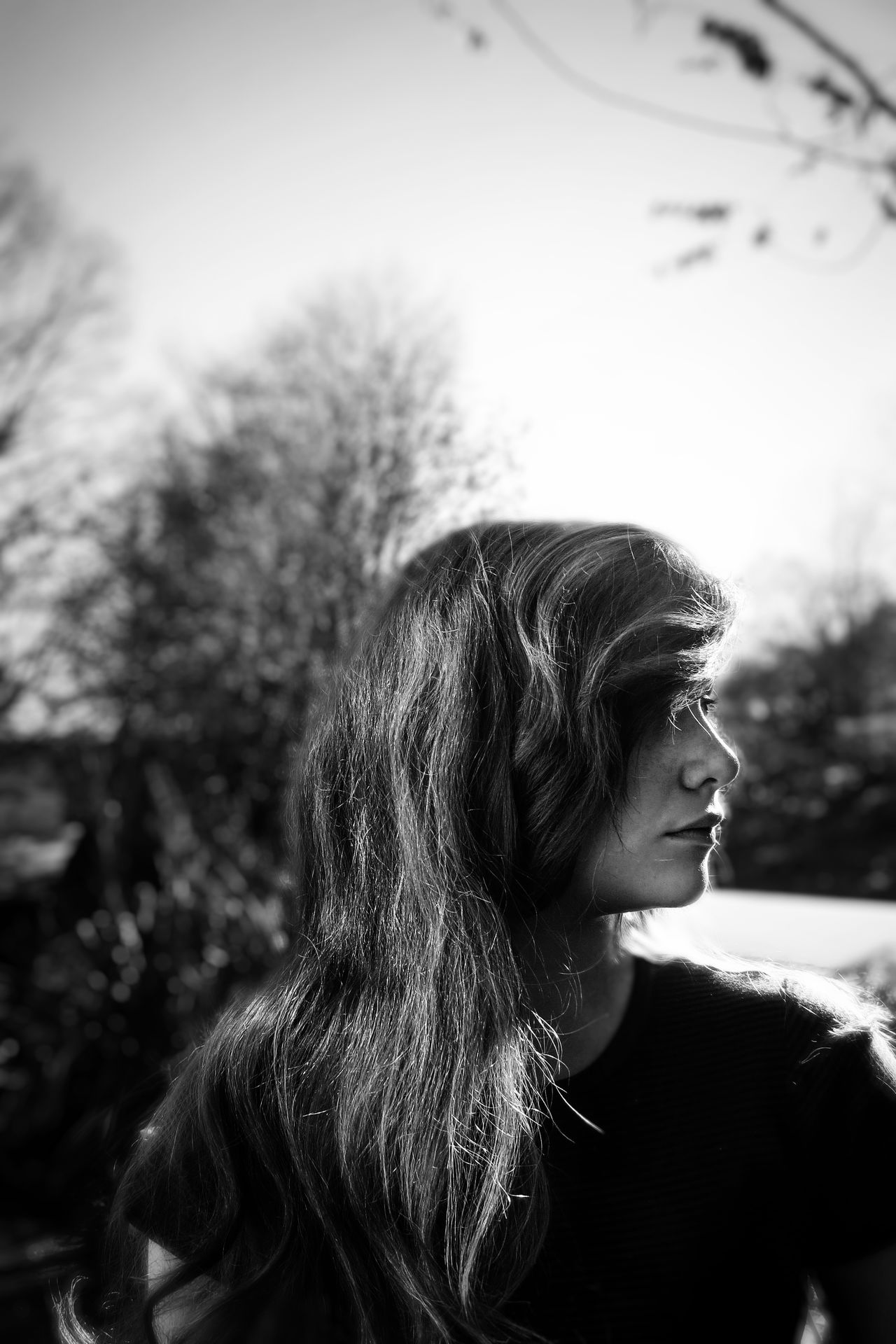 Close-up of woman looking away while standing against bare trees