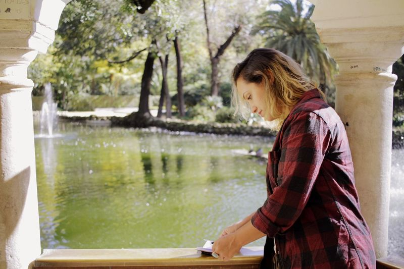 Woman writing on diary at balcony by pond