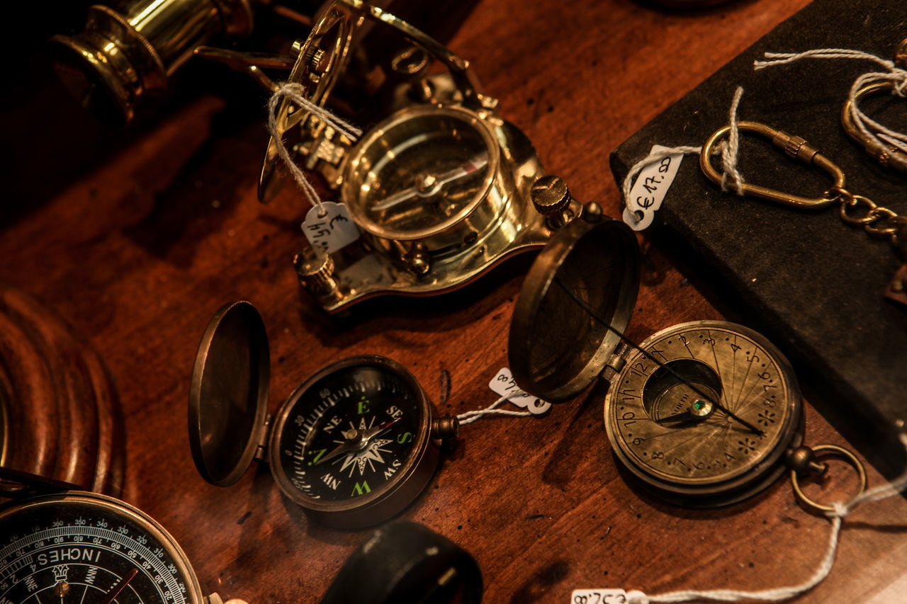 High Angle View Of Antique Compasses With Labels On Table At Store