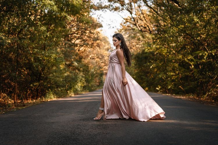 Full length of woman standing on road amidst trees