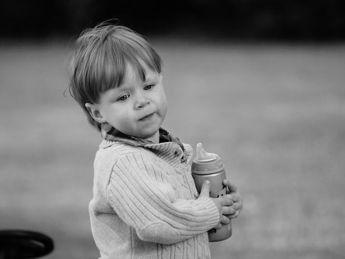 Cute Boy Holding Milk Bottle While Standing Outdoors