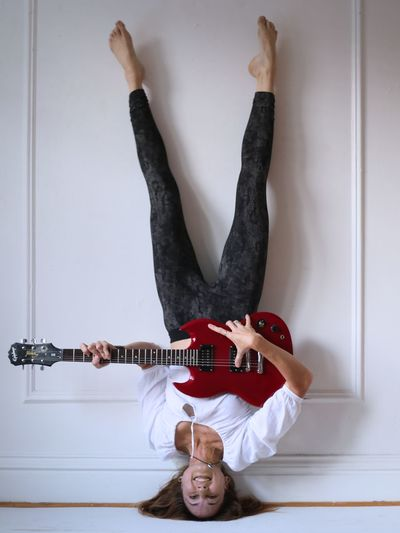 Woman Doing Headstand And Playing Guitar Against Wall