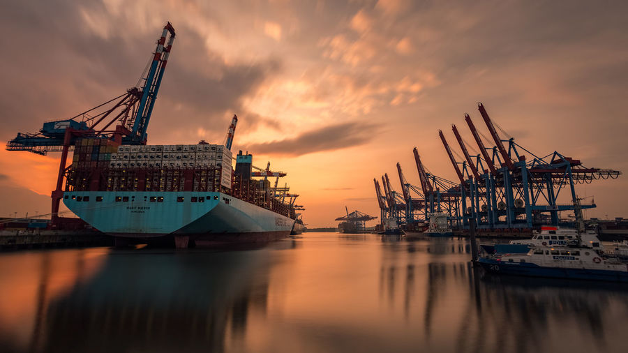 Cargo Container Cloud - Sky Commercial Dock Crane - Construction Machinery Day Freight Transportation Harbor Industry Mode Of Transport Moored Nature Nautical Vessel No People Outdoors Reflection Sea Shipping  Shipyard Sky Sunset Transportation Water Waterfront