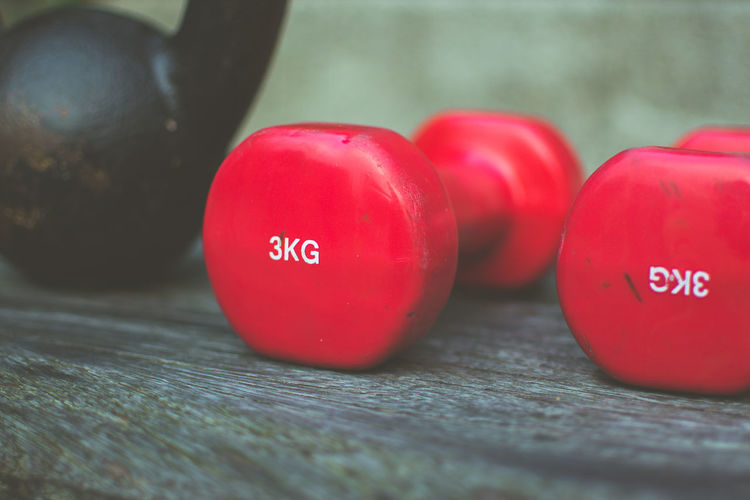 Close-Up Of Kettlebell And Dumbbells On Wooden Table