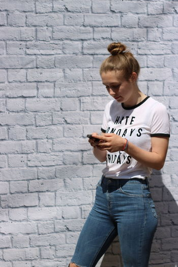 Teenage Girl Using Mobile Phone While Standing Against Brick Wall