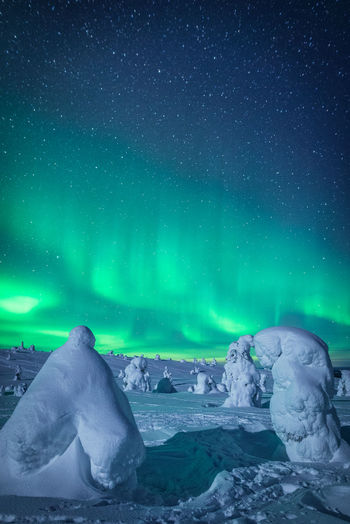 Scenic view of snow covered land against sky during aurora borealis