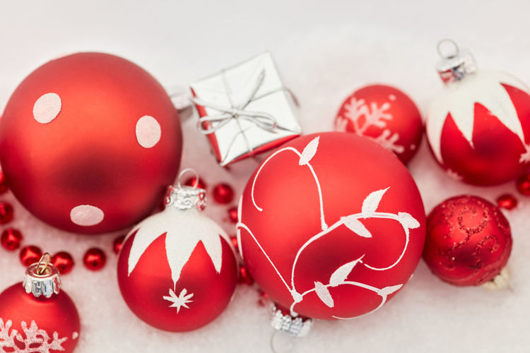 Close-up of red christmas baubles and gift box on snow