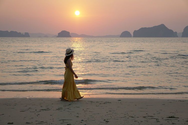 Side view of woman waling on beach during sunset