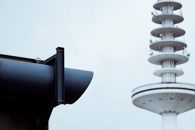 Low angle view of coin-operated binoculars by air traffic control tower against sky