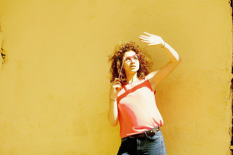 Young woman holding eye mask prop while standing against wall during sunny day