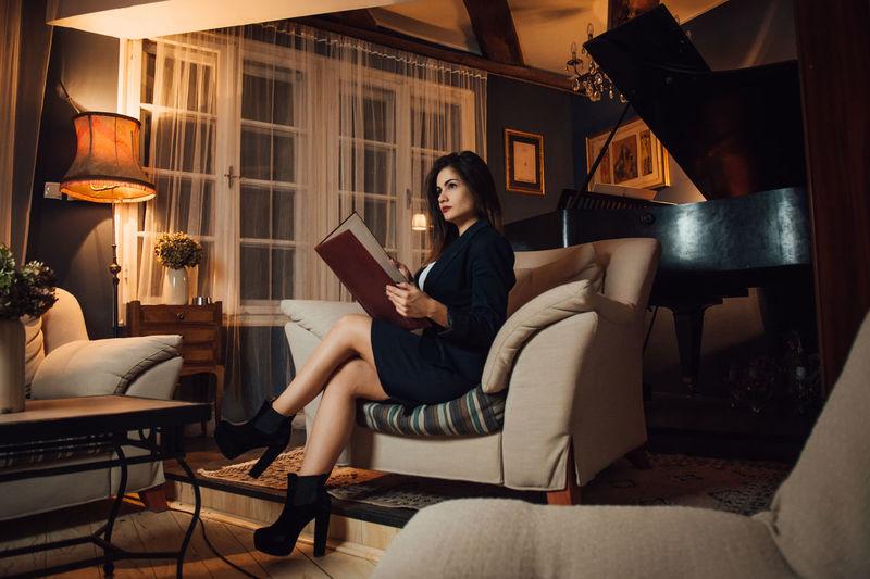 Sitting Sofa Indoors  Young Women Full Length Young Adult Women Publication Furniture Real People One Person Adult Leisure Activity Book Lighting Equipment Legs Crossed At Knee Lifestyles Relaxation Reading Coffee Table Electric Lamp Beautiful Woman