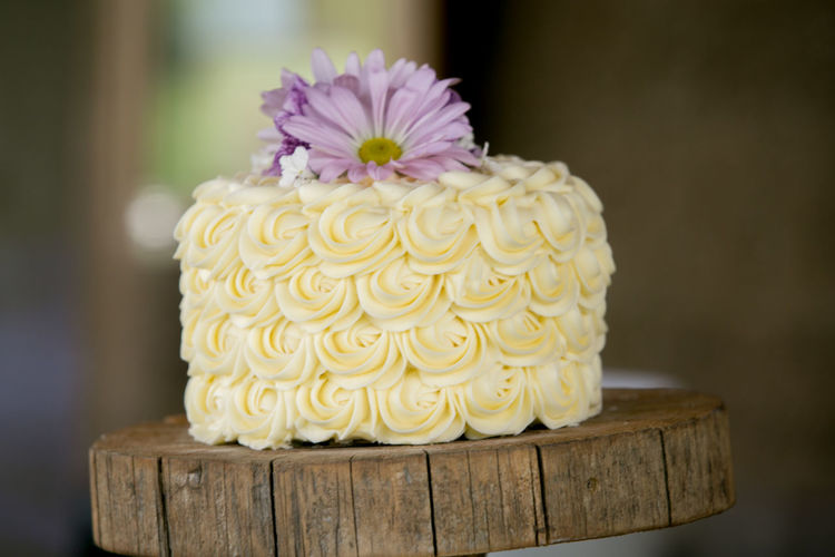 Close-Up Of Wedding Cake On Wooden Stand