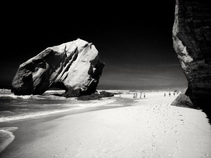 Rock formations on beach against clear sky