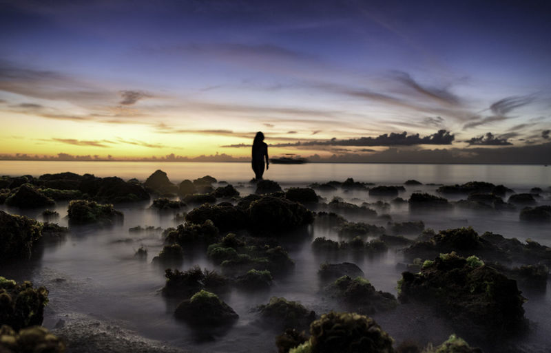 Silhouette woman standing by sea against sky during sunset