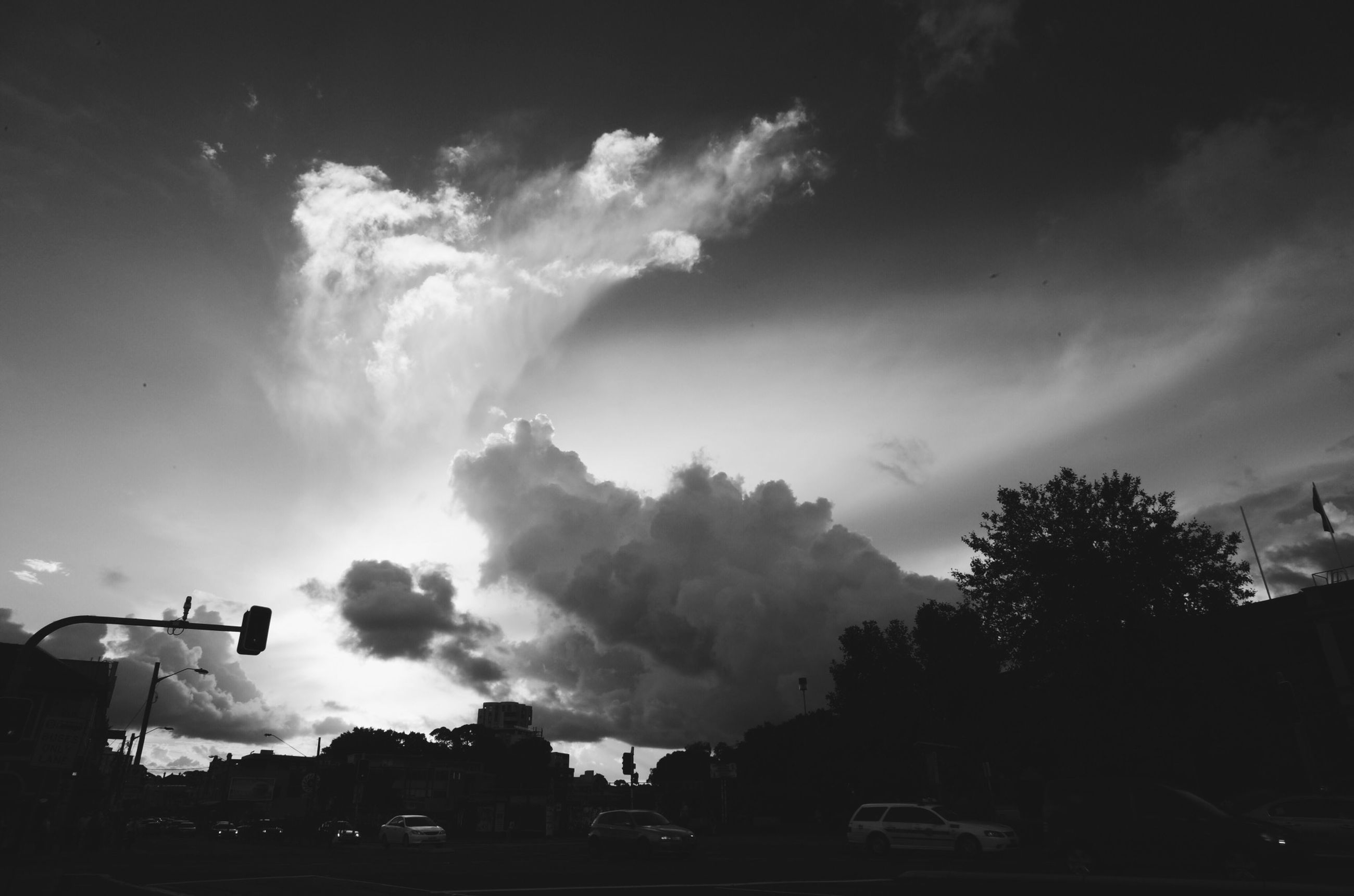 sky, building exterior, cloud - sky, built structure, architecture, low angle view, silhouette, cloudy, tree, transportation, street light, car, cloud, dusk, land vehicle, house, mode of transport, city, outdoors, overcast