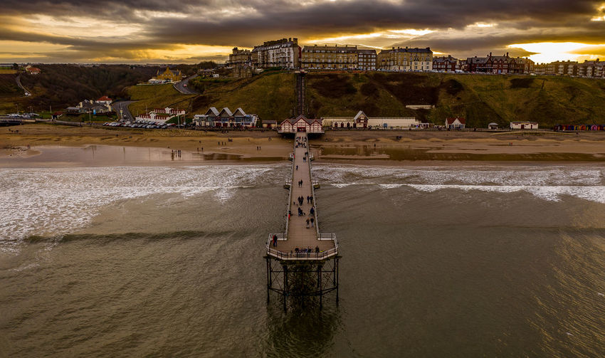 Opened in 1869, Saltburn Pier is 460 m long of iron construction Water Architecture Built Structure Cloud - Sky Sky Nature Land Building Exterior Sunset Sea Beauty In Nature Outdoors Travel Destinations Travel Dusk Beach Mountain Scenics - Nature Incidental People Drone  Sunsets Saltburn Pier Seascape Seaside Beach Photography