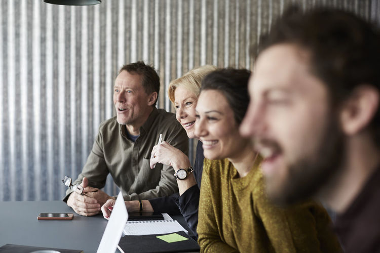 Smiling creative business colleagues sitting at conference table while looking away in board room