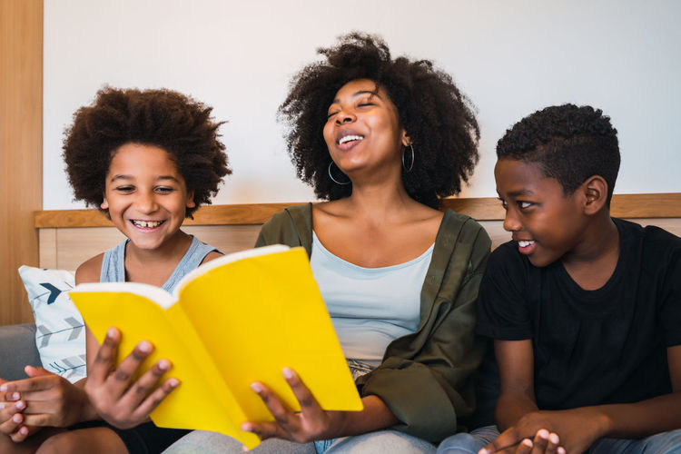 Young woman sitting with boys reading book at home