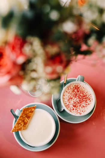 Two delicious cups of cappuccino latte with foam on the pink table in the cafe for breakfast