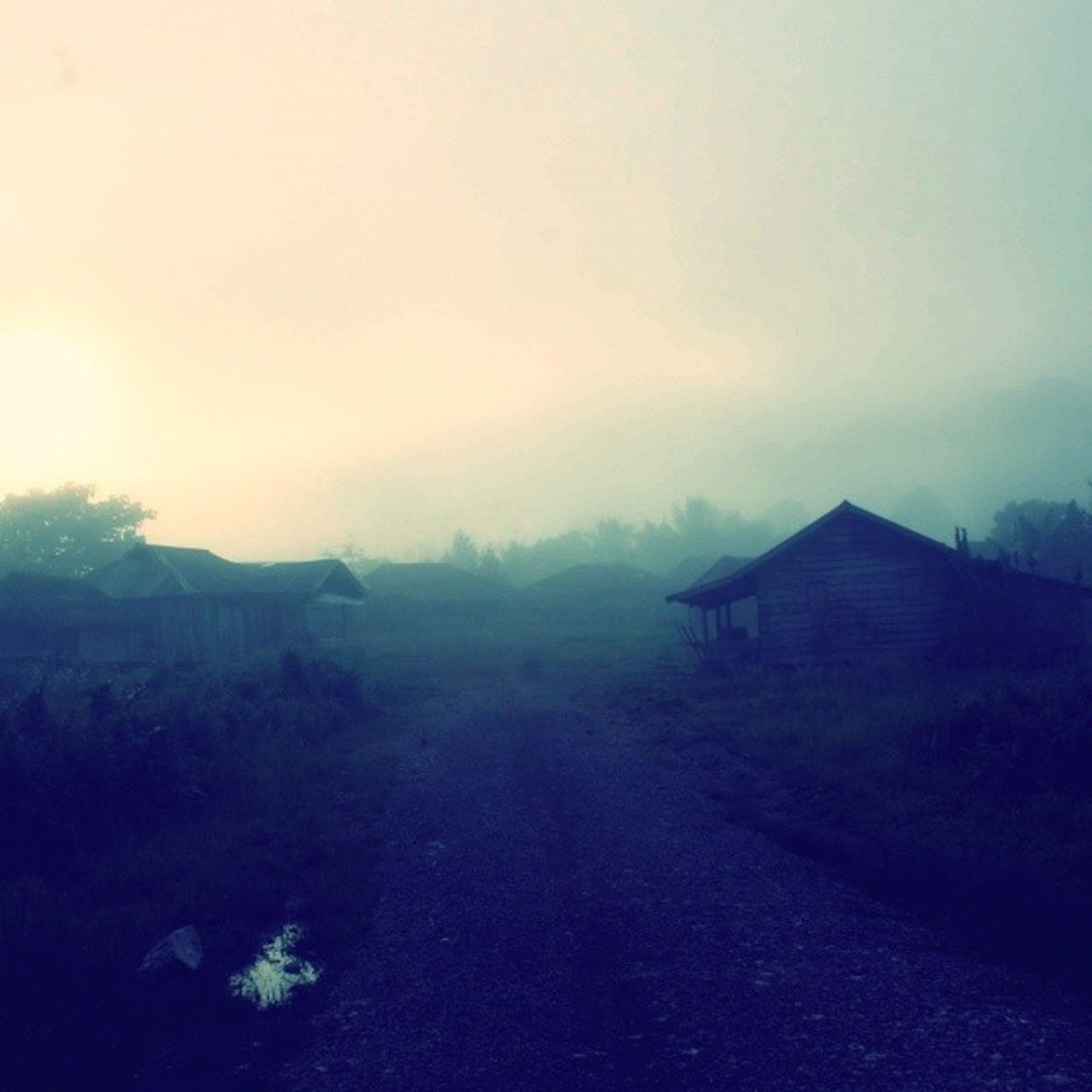 building exterior, built structure, fog, architecture, sky, tranquility, landscape, tranquil scene, house, weather, foggy, scenics, beauty in nature, nature, copy space, mountain, sunset, field, outdoors, no people