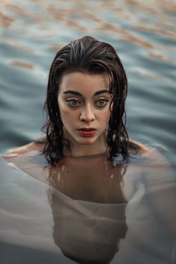 Portrait of a beautiful young woman in water