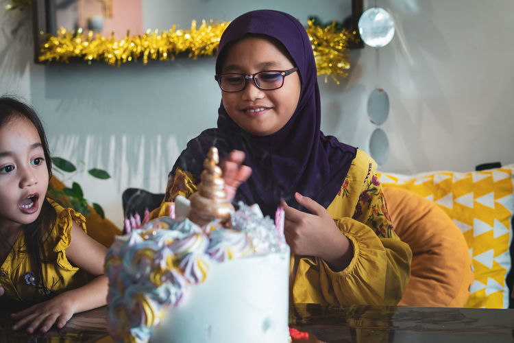 Smiling girl looking at cake while sitting with friend at home
