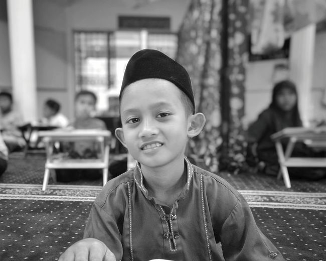 Portrait of smiling boy in traditional clothing at home