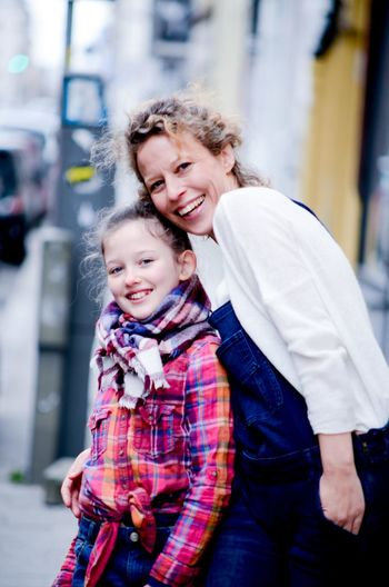 Portrait Of Cheerful Grandmother And Granddaughter In City