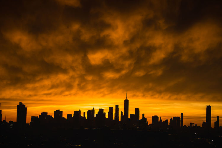 An incredible view of the city skyline after a massive thunderstorm in New York City Silhouette Architecture Building Building Exterior Built Structure City Cityscape Cloud - Sky Financial District  Modern No People Orange Color Sky Skyscraper Sunset Tall - High Tower Travel Destinations Urban Skyline