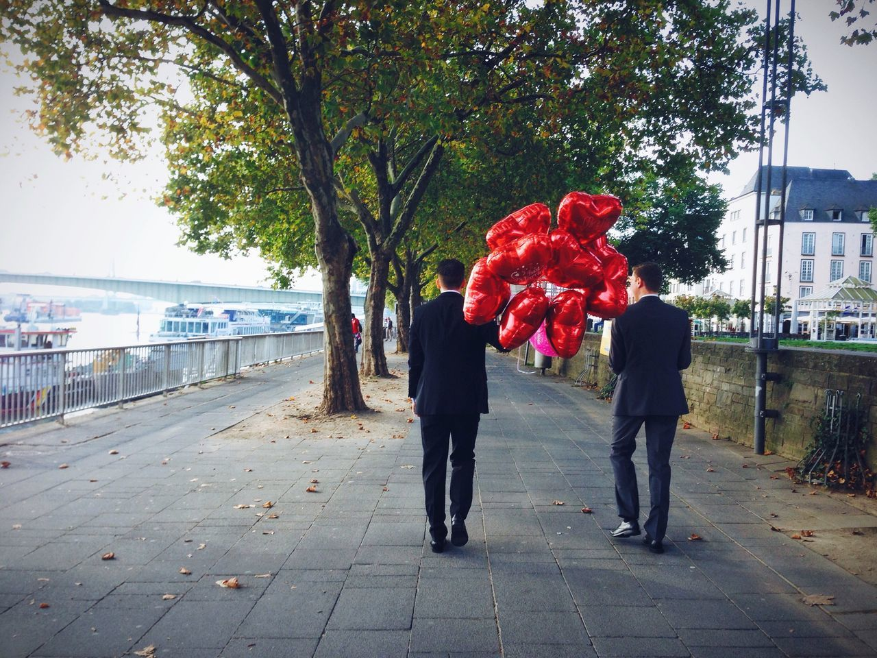 Rear view of gay couple walking with balloons