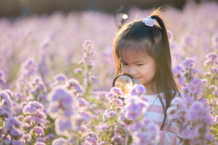 Close-up of girl against purple flowering plants