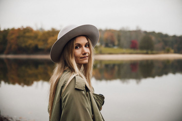 Portrait of woman wearing hat standing by lake against sky