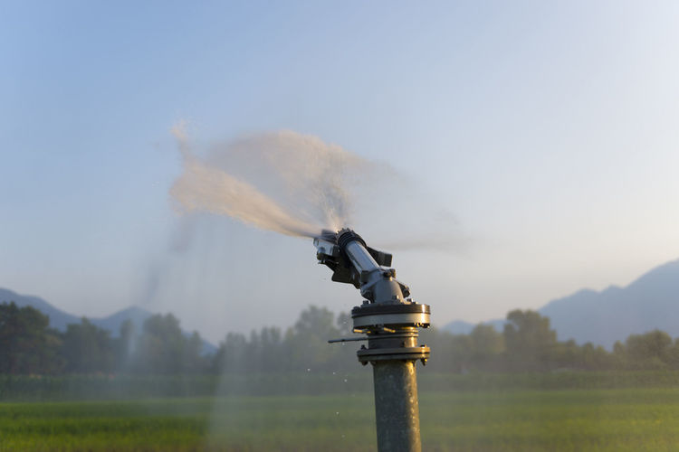 Water Sprinkler in a Wheat Field Agriculture Clear Sky Motion Blur Sunlight Agricultural Machinery Close Up Day Daylight Firefighter Focus On Foreground Irrigation Equipment Landscape Motion Nature Outdoors Sky Spraying Sprinkler Water Wet
